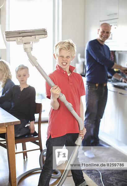 Porträt eines Jungen  der die Zähne zusammenbeißt  während er den Staubsauger zu Hause hält.