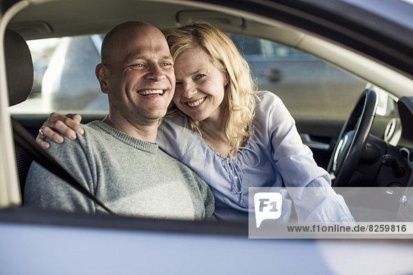 Porträt einer glücklichen Frau mit Mann im Auto