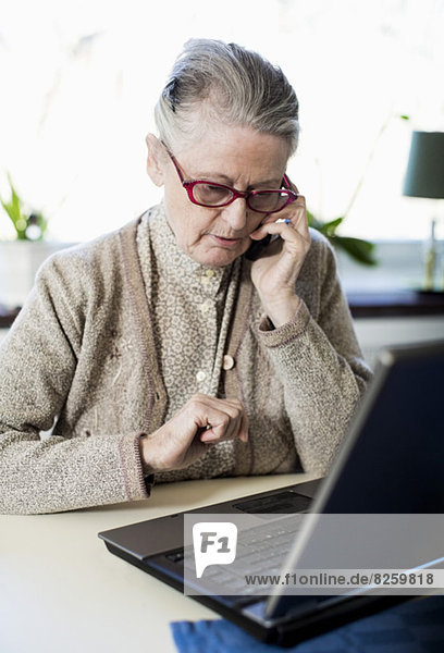 Senior woman using mobile phone while sitting with laptop on table