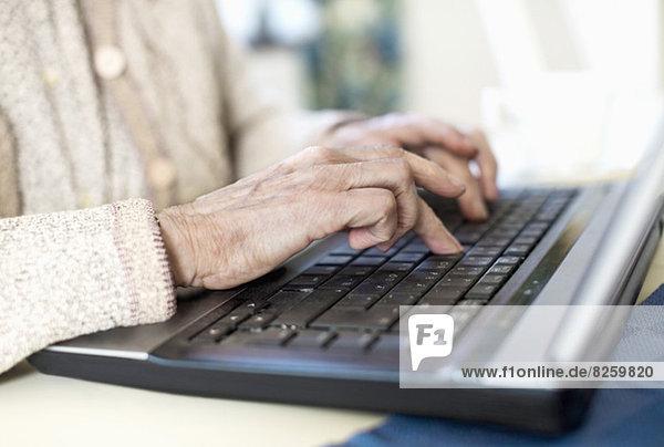 Mittelteil der älteren Frau mit Laptop zu Hause