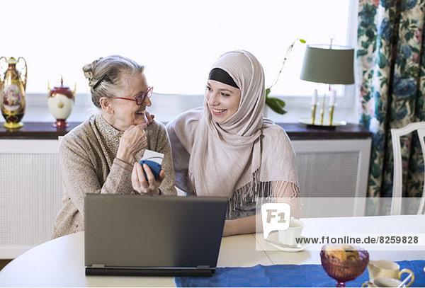 Fröhliche junge Hausfrau mit älterer Frau bei einer Banküberweisung am Laptop