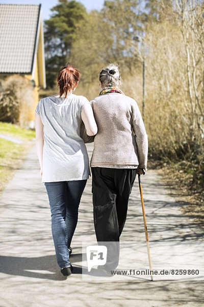 Rückansicht der älteren Frau und der Betreuerin im Haus  die Arm in Arm auf der Straße gehen