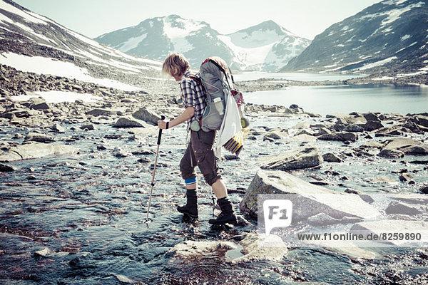 Seitenansicht der Wanderin beim Überqueren des Flusses
