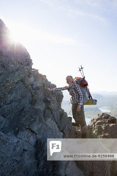 Porträt einer glücklichen Kletterin  die auf Felsen gegen den Himmel steht.