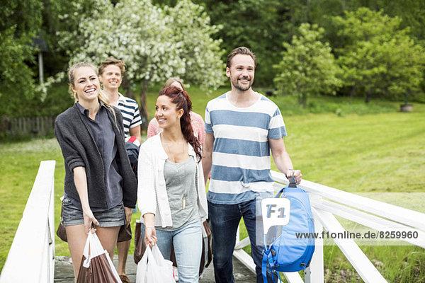 Gruppe von glücklichen Freunden mit Gepäck  die mit dem Geländer im Park spazieren gehen.