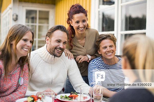 Glückliche Freunde beim Essen im Sommerhaus