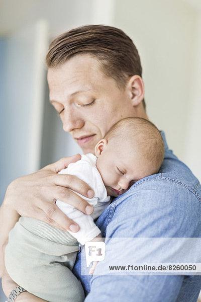 Vater trägt Baby zu Hause