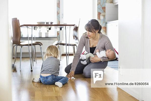 Mutter putzt den Boden mit der Tochter und hält das Baby zu Hause.