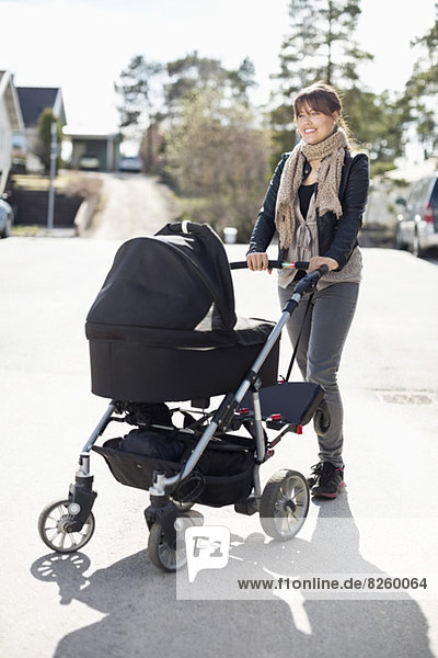 Glückliche Frau mit Kinderwagen auf sonniger Straße stehend