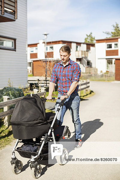 Mittelgroßer Mann mit Kinderwagen auf sonniger Straße