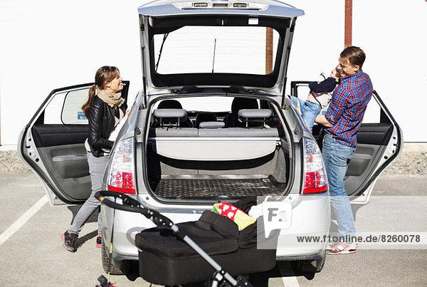 Familie  die auf der Straße ins Auto steigt