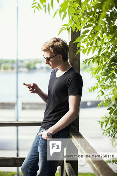 Junger Mann mit Handy auf dem Balkon