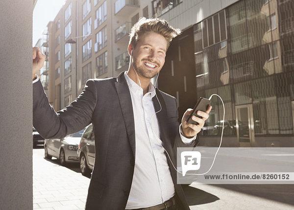 Glücklicher junger Geschäftsmann  der Musik über das Handy auf der Straße hört.