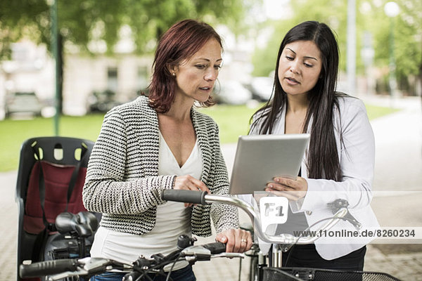 Geschäftsfrauen mit Fahrrädern mit digitalem Tablett auf der Straße