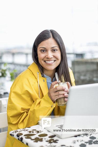 Portrait der Geschäftsfrau mit Laptop auf dem Tisch mit Milchshake im Cafe