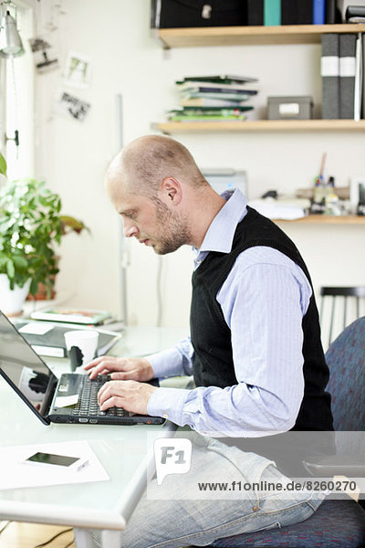 Mid adult businessman using laptop at desk in office