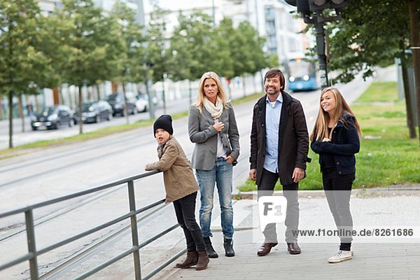 Family with two kids waiting for tram