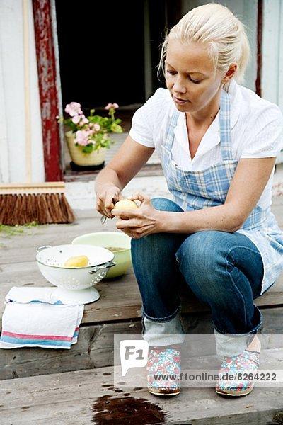 Young woman peeling potatoes