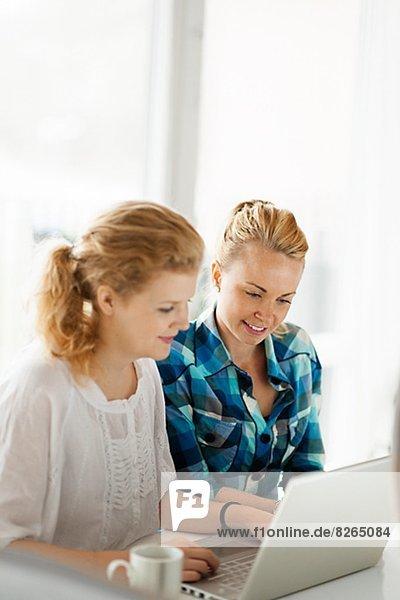 Zwei junge Frauen arbeiten auf laptop
