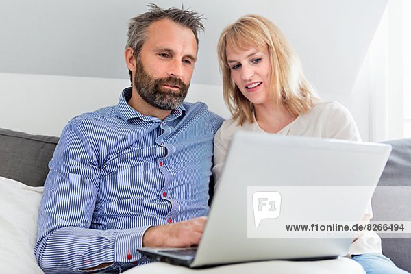 Mid adult couple using laptop
