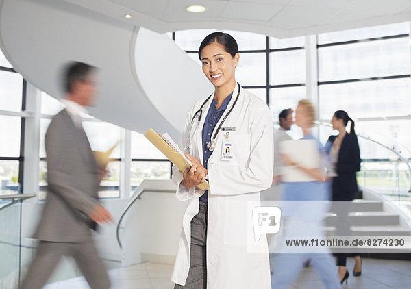 Porträt des lächelnden Arztes im Krankenhausatrium
