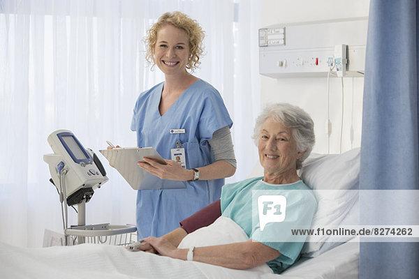 Porträt der lächelnden Krankenschwester und des älteren Patienten im Krankenhauszimmer