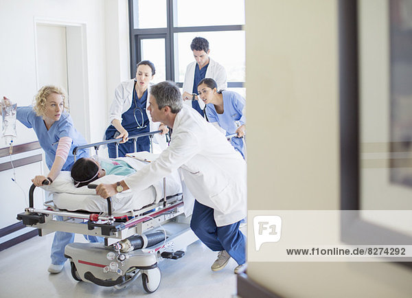 Ärzte und Krankenschwestern hetzen Patienten auf Bahre den Krankenhausflur hinunter