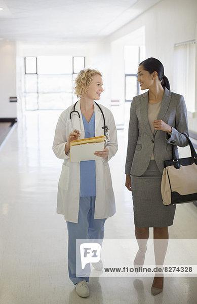 Ärztin und Geschäftsfrau beim Spaziergang im Krankenhausflur