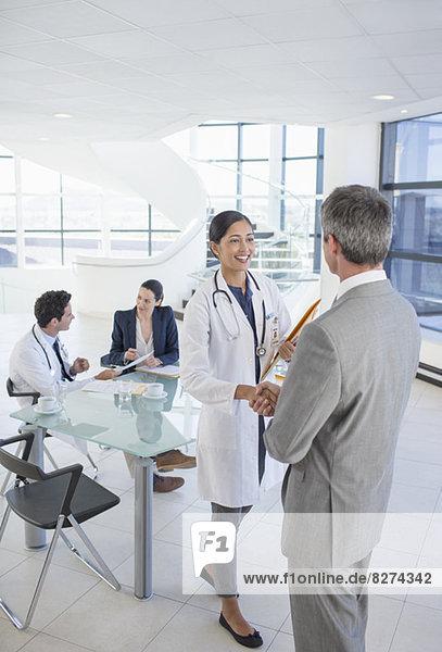 Arzt und Geschäftsmann schütteln sich die Hand bei einem Treffen