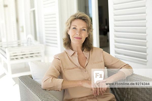 Porträt einer lächelnden älteren Frau auf der Terrasse