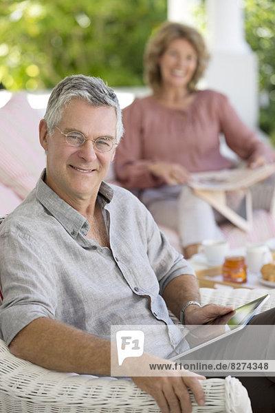 Senior Mann mit digitalem Tablett im Sessel auf der Terrasse