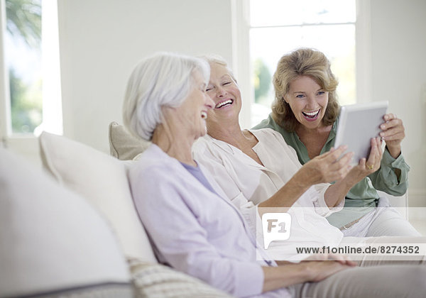 Older women using digital tablet on sofa