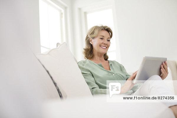Seniorin mit digitalem Tablett auf dem Sofa