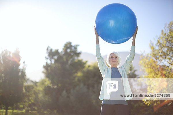Seniorin mit Fitnessball im Park
