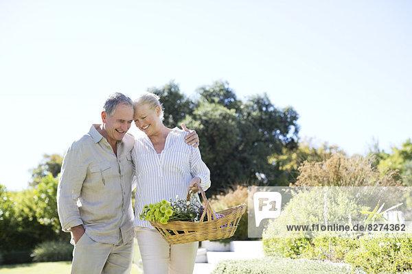 Seniorenpaar zu Fuß mit Korb im Freien