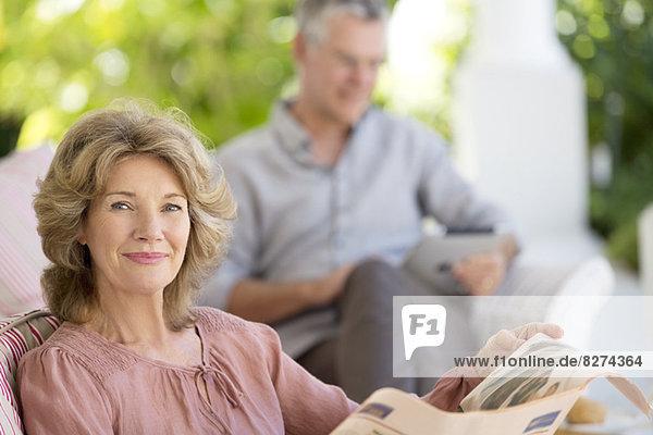 Seniorin beim Zeitungslesen auf der Terrasse