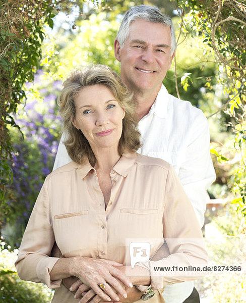 Porträt eines lächelnden Seniorenpaares beim Umarmen im Freien
