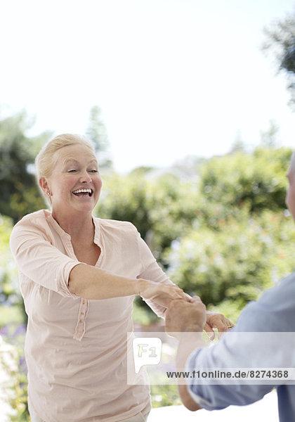 Seniorenpaar tanzt auf der Terrasse