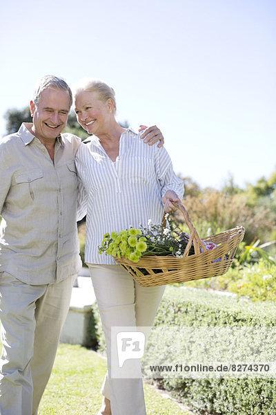 Seniorenpaar beim Spaziergang im Garten mit Blumenkorb