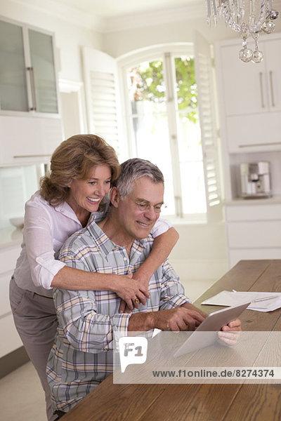 Seniorenpaar mit digitalem Tablett in der Küche