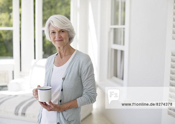 Seniorin hält eine Tasse Kaffee im Wintergarten.