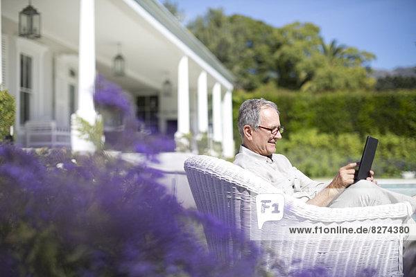 Senior Mann mit digitalem Tablett im Garten