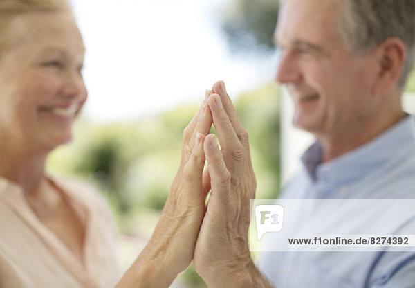 Seniorenpaar berührt Hände auf der Terrasse