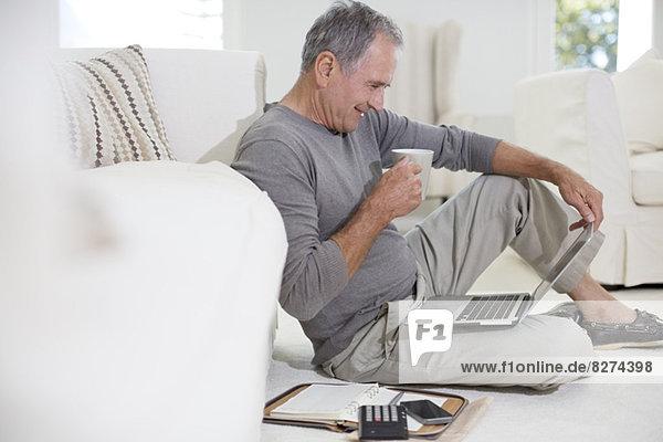 Senior Mann mit Laptop auf dem Wohnzimmerboden