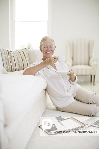 Seniorin trinkt Kaffee auf dem Wohnzimmerboden