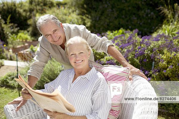 Seniorenpaar beim Zeitungslesen im Garten