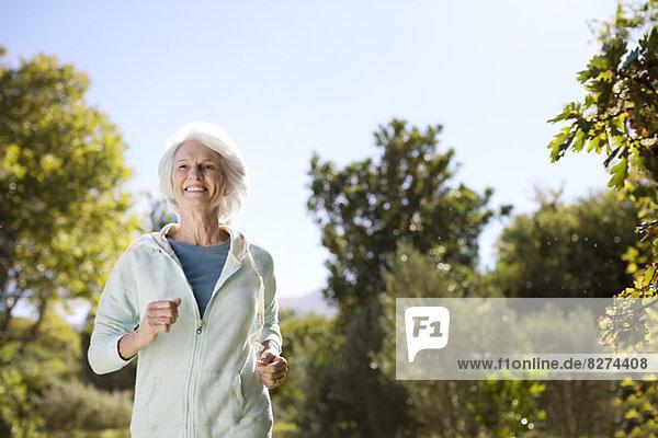 Seniorin läuft im Park