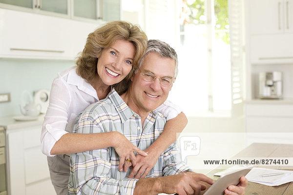 Porträt eines lächelnden Seniorenpaares mit digitalem Tablett in der Küche