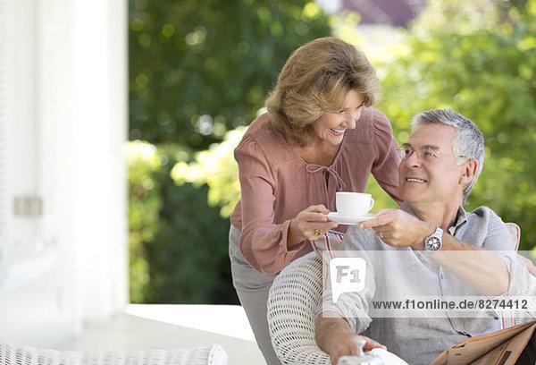 Seniorenfrau bringt Mann eine Tasse Kaffee auf die Terrasse