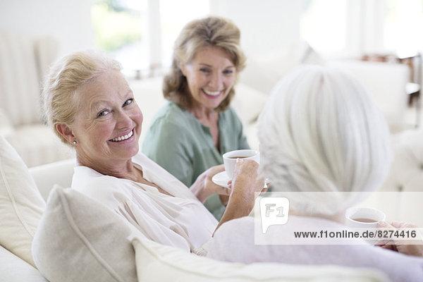 Seniorinnen trinken Kaffee auf dem Sofa